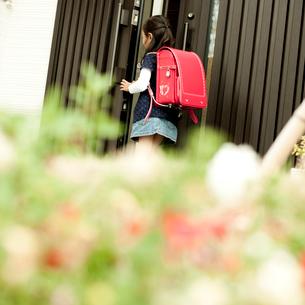 ドアを開けるランドセルを背負った女の子の写真素材 [FYI02051612]