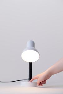 卓上ライトのスイッチを押す手の写真素材 [FYI02051650]