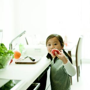 キッチンでトマトを持つ女の子の写真素材 [FYI02051661]