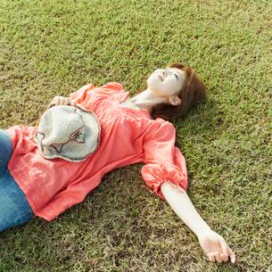 芝生で横になる女性の写真素材 [FYI02051681]