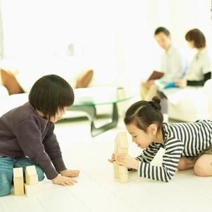 積み木で遊ぶ2人の子供とソファに座る両親の写真素材 [FYI02051698]