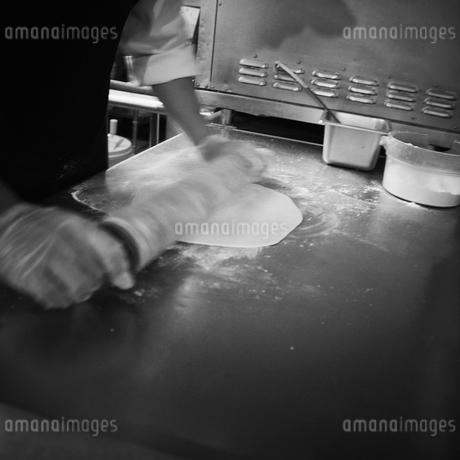 ピザの生地を伸ばす人の手元の写真素材 [FYI02051759]