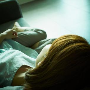 ソファに横たわる女性の写真素材 [FYI02051772]