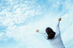 空へ向かい伸びをするビジネスウーマンの写真素材 [FYI02051776]