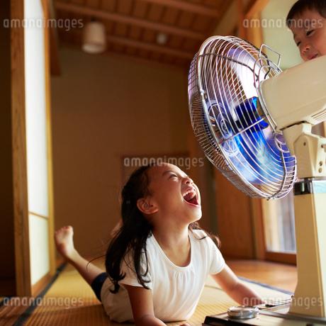 扇風機の前で口を開ける女の子の写真素材 [FYI02051954]