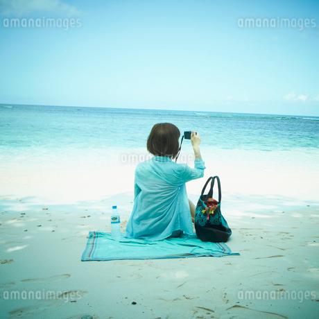 海に向かってカメラを構える女性の写真素材 [FYI02052042]