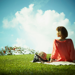 芝生に座る女性の後姿の写真素材 [FYI02052208]
