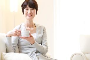 コーヒーカップを持ちソファに座るシニア女性の写真素材 [FYI02052235]