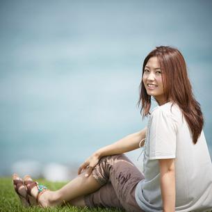 芝生の上に座り振り向く女性の写真素材 [FYI02052252]