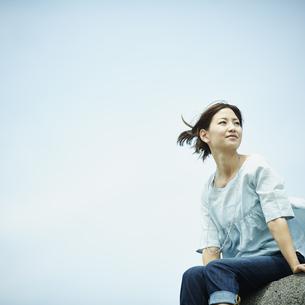 防波堤に座る女性と青空の写真素材 [FYI02052296]