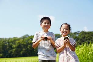 田園でおにぎりを食べる男の子と女の子の写真素材 [FYI02052326]