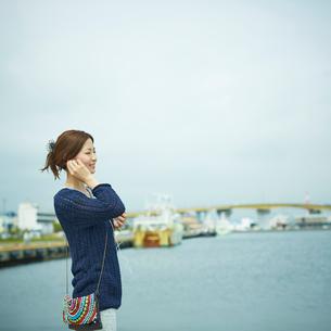 港で音楽を聴く女性の写真素材 [FYI02052409]