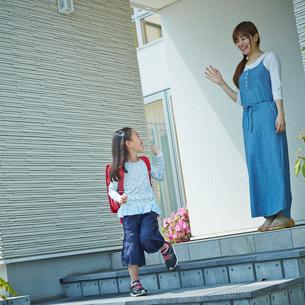 手を振るランドセルを背負った女の子と見送る母親の写真素材 [FYI02052431]