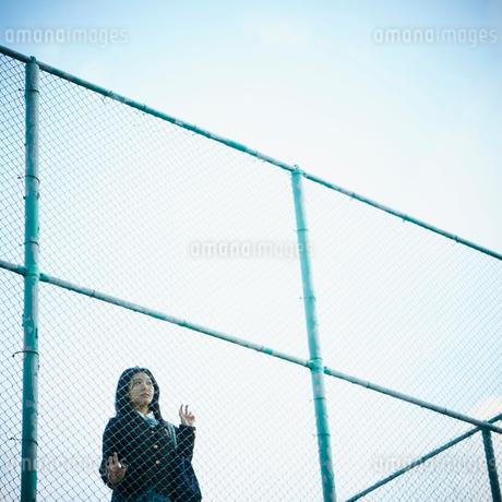 フェンス越しに外を眺める女子学生の写真素材 [FYI02052456]
