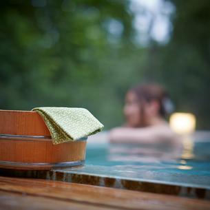 露天風呂の風呂桶と入浴する女性の写真素材 [FYI02052564]