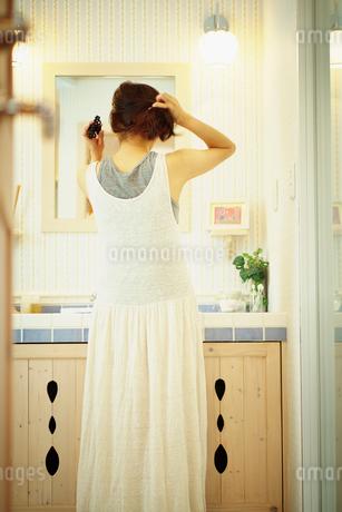 洗面所で髪をまとめる女性の後ろ姿の写真素材 [FYI02052621]