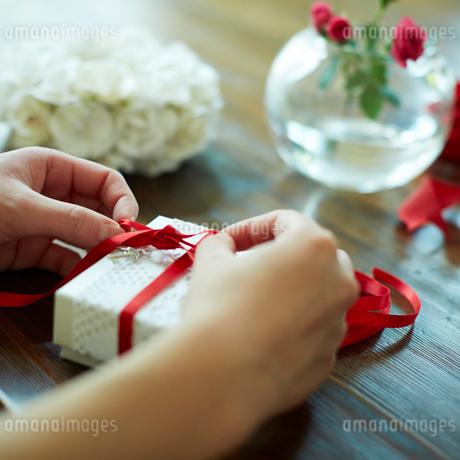 ギフトボックスにリボンを結ぶ女性の手元の写真素材 [FYI02052627]