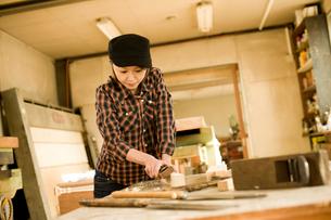 鉋で木材を削る女性の写真素材 [FYI02052695]