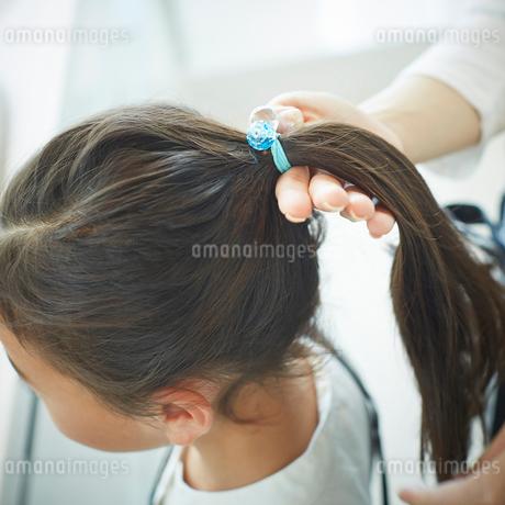 女の子の髪を結う母親の手の写真素材 [FYI02052701]