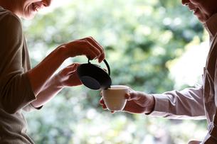 急須でお茶を淹れるシニア夫婦の手元の写真素材 [FYI02052706]
