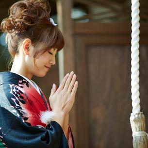 神社で手を合わせる振袖姿の女性の写真素材 [FYI02052714]