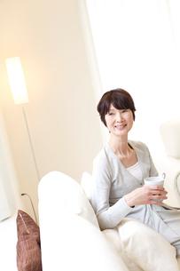 コーヒーカップを持ちソファに座るシニア女性の写真素材 [FYI02052812]