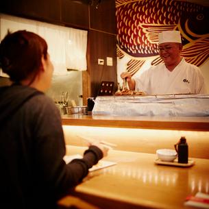 カウンターで向い合う料理人と女性客の写真素材 [FYI02052840]
