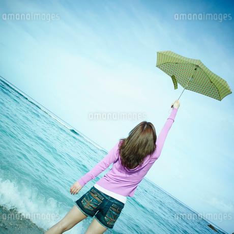 傘を空に掲げる女性と海の写真素材 [FYI02052841]