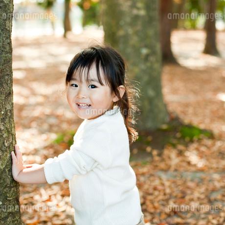木の幹に手をつく笑顔の女の子の写真素材 [FYI02052889]
