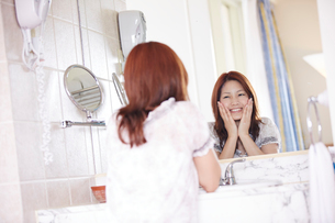 鏡に向かい頬に手をあてる女性の写真素材 [FYI02052908]