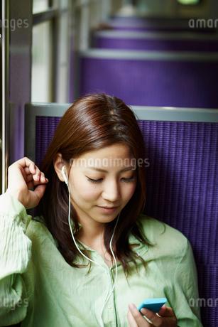 列車の中で音楽を聴く女性の写真素材 [FYI02052928]