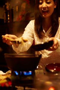 せんべい汁を取り分ける女性の写真素材 [FYI02052943]