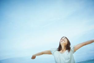 空を見上げ伸びをする女性の写真素材 [FYI02052962]