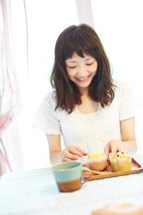 食卓に座る笑顔の若い女性の写真素材 [FYI02052998]