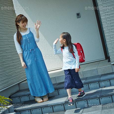 手を振るランドセルを背負った女の子と見送る母親の写真素材 [FYI02053013]