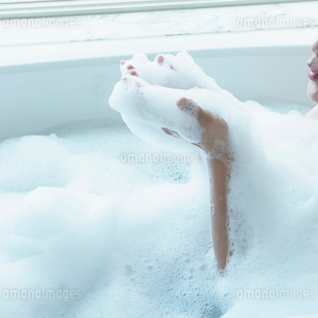 泡風呂の泡に息を吹きかける女性の写真素材 [FYI02053020]