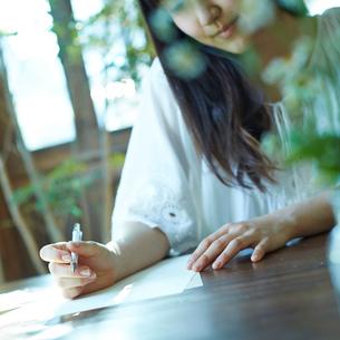 手紙を書く女性の写真素材 [FYI02053026]