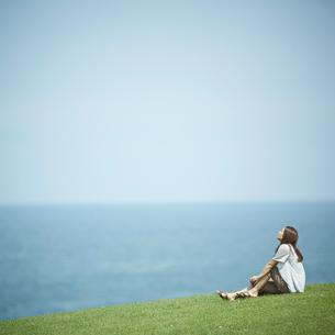 芝生の上に座る女性と海の写真素材 [FYI02053051]