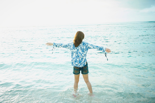 海で両腕を広げる女性の後姿の写真素材 [FYI02053054]