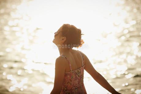 海面に反射する光と女性の写真素材 [FYI02053067]