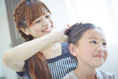 女の子の髪を結う母親の写真素材 [FYI02053072]