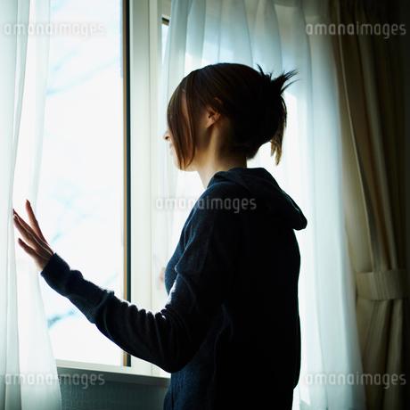 カーテンを開ける女性の写真素材 [FYI02053092]