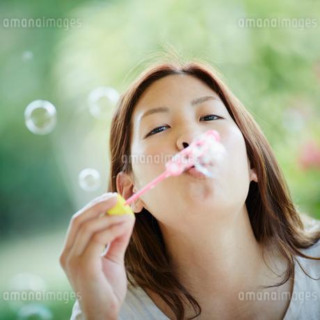 シャボン玉を吹く女性の写真素材 [FYI02053094]