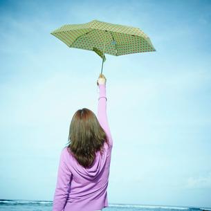 傘を空に掲げる女性の後姿の写真素材 [FYI02053105]