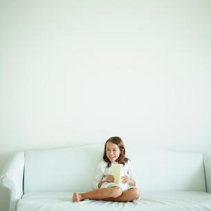 ソファに座り本を読む女の子の写真素材 [FYI02053112]