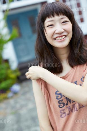 Tシャツの袖を肩口までまくる若い女性の写真素材 [FYI02053165]