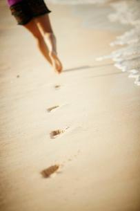 砂浜を歩く女性の足元と足跡の写真素材 [FYI02053193]