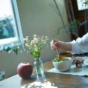 サラダを食べる女性の手とテーブルの上の花とリンゴの写真素材 [FYI02053195]