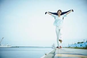 伸びをしながら港を歩く女性の写真素材 [FYI02053222]
