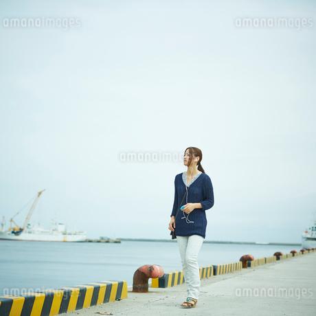 音楽を聴きながら港を歩く女性の写真素材 [FYI02053240]